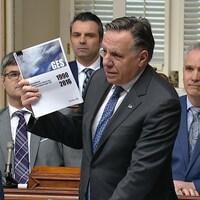 François Legault tient dans ses mains le plus récent bilan des émissions de GES du ministère de l'Environnement.