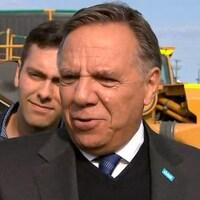 François Legault s'adresse aux médias devant un gros camion de couleur orange.