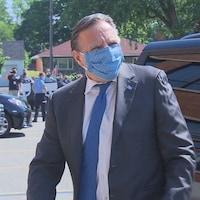 Le premier ministre François Legault sort d'une voiture dans un stationnement. Il porte un couvre-visage.