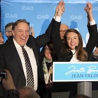 Trois personnalités politiques triomphantes sur une scène.