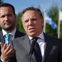 François Legault, entouré de deux candidats, lors d'un point de presse à l'extérieur.