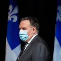 François Legault, de profil, porte un masque.