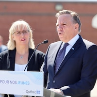 François Legault prend la parole lors d'une conférence de presse organisée dans la cour de l'école L'Accueil. Il se tient derrière un lutrin muni d'un microphone. Il est accompagné de la directrice Sylvie Boutin.