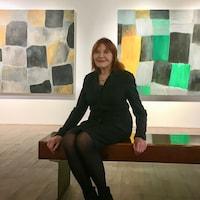 La femme est assise sur un banc, placé devant ses toiles, et elle sourit.