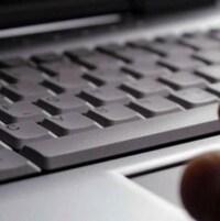 Une main devant un clavier d'ordinateur.