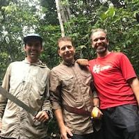 Trois hommes munis de machettes sourient à la caméra.