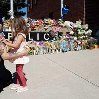 Une femme et une fillette observent un mémorial devant un poste de police à Fredericton le 11 août 2018.