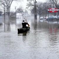 Un homme sur un canot dans la rue inondée.