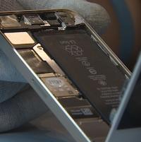 Une photo d'un iPhone dont l'écran est en train d'être retiré par une personne dont on ne voit pas le visage.