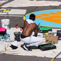 Des gens, agenouillés, s'affairent à peinturer un terrain de basketball de toutes sortes de couleurs.