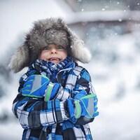 Un petit garçon dehors, un jour d'hiver.