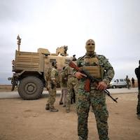 Un soldat masqué porte une arme au premier plan. Au second est posté un véhicule blindé.