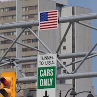 Une affiche indique le passage pour voiture vers les États-Unis. Le feu de circulation est au  rouge.