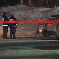 Deux policiers et des voitures de police, derrière un ruban rouge, à l'endroit où on a retrouvé une fugueuse morte, à Laval.