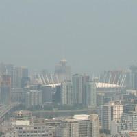 Plusieurs immeubles vus de loin et de haut, dont le stade Rogers, enveloppés de fumée, on ne voit pas du tout les montagnes au-delà de la ville.