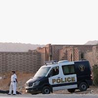 Deux policiers égyptiens se tiennent devant une voiture de police.