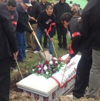 Des gens déposent le cercueil de Chrsitine Wood sous terre.