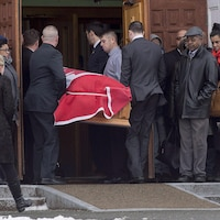 Des porteurs entrent dans l'église avec le cercueil de Lionel Desmond, recouvert d'un drapeau du Canada.