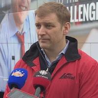 Andrew Furey interviewé devant son autobus de campagne.