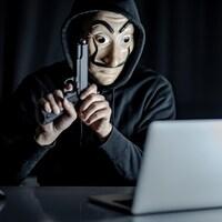 Une personne masquée manie un pistolet devant un ordinateur portable.