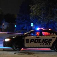 Une voiture de police stationnée devant le périmètre de sécurité, à Laval.