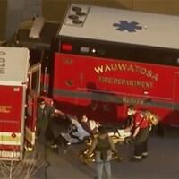 Deux blessés sur des civières à côté de véhicules d'urgence.