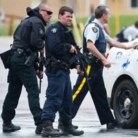 Des policiers armés gardent une rue.