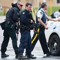 Des policiers armés gardent une rue