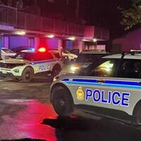 Plusieurs voitures de police près d'un édifice résidentiel la nuit.