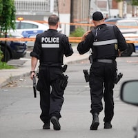 Deux policiers du SPVM, de dos, marchent sur une scène de crime.