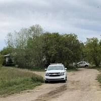 Des voitures de police sont stationnées près d'une maison cachée par la végétation.