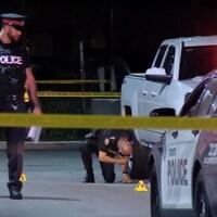 Deux policiers regardent au sol derrière un périmètre de sécurité.