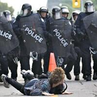 Le protestataire est couché sur le ventre, avec derrière lui un mur de policier en marche.