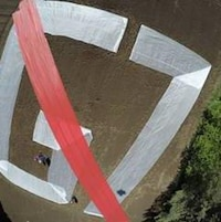 G7 traversé d'une barre rouge inscrit sur le sol dans un champs et visible du haut des airs