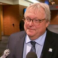 Gaétan Barrette répond aux questions des journalistes lors d'une mêlée de presse dans les couloirs du Centre des congrès de Québec.