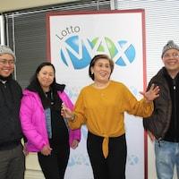 Quatre personnes joyeuses debout devant une pancarte Lotto Max.