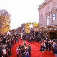 Vue aérienne d'un tapis rouge devant un théâtre avec une foule de spectateurs et spectatrices de chaque côté.