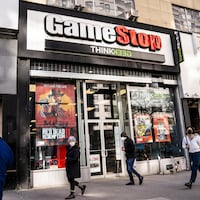 Des passants marchent devant un magasin GameStop à New York.