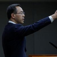 M. Feng, le bras gauche levé, lors d'un point de presse devant le drapeau chinois.