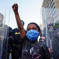 Un garçonnet noir lève le poing, devant des policiers protégés par des boucliers