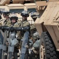 Des militaires de la garde nationale, en poste entre deux véhicules blindés.