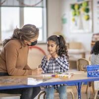 Une éducatrice attablée à côté d'une fillette dans une garderie.