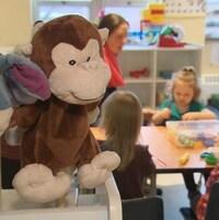 Des jouets sont à l'avant-plan de la photo qui montrent aussi une éducatrice assise à une table avec des enfants