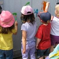 Des enfants de dos dessinant sur une clôture.