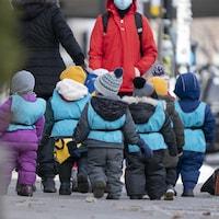De jeunes enfants dehors et habillés chaudement marchent avec leurs surveillantes.