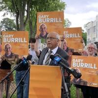 Un homme vêtu d'un complet foncé parle à une tribune, entouré de personnes qui brandissent des affiches électorales.