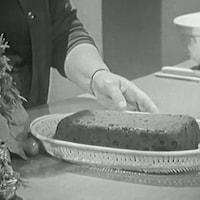 Un gâteau aux fruits est posé dans une corbeille, près de décorations de Noël.