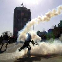 Un manifestant relance une grenade de gaz lacrymogène en direction des policiers.