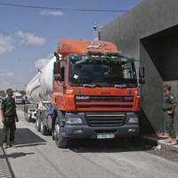 Un camion-citerne arrêté à un poste frontalier, entouré de trois militaires