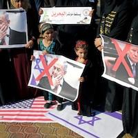 Des enfants tiennent une photo sur laquelle un X rouge est tracé sur le premier ministre israélien Benyamin Nétanyahou. Une autre photo du président américain Donald Trump est aussi marquée d'un X rouge.